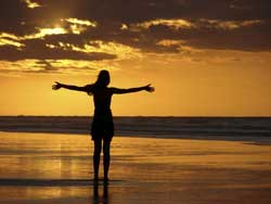 vision exercises: woman at sunset with outstretched arms