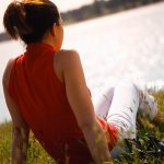 Journaling Exercise shown by woman sitting on grass watching a lake