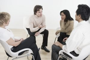 Group Coaching - 4 people sat down having a discussion