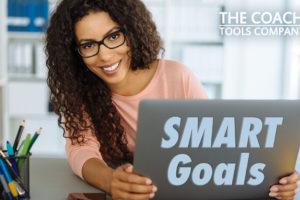 Coach peers round laptop saying SMART Goals