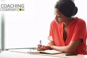 Leader journaling at desk wearing orange shirt
